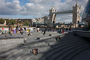 Lunchtime women talk with a background panorama looking north from More London in Southwark, towards Tower Bridge, on 6th October 2016, in London, England.