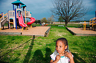 """Kodie Brown plays at the local playground, near RFK Stadium. Kodie's mother was fatally shot by her father while trying to escape onto a Metro bus. Kodie, who was grazed by a bullet in the attack, needs several operations to remove more facial scar tissue. """"No baby should have to go through what she has gone through,"""" said Deborah Alessi, who has helped set up a foundation that pays for victims of domestic violence to have plastic surgery. (Amanda Voisard, for The Washington Post )"""