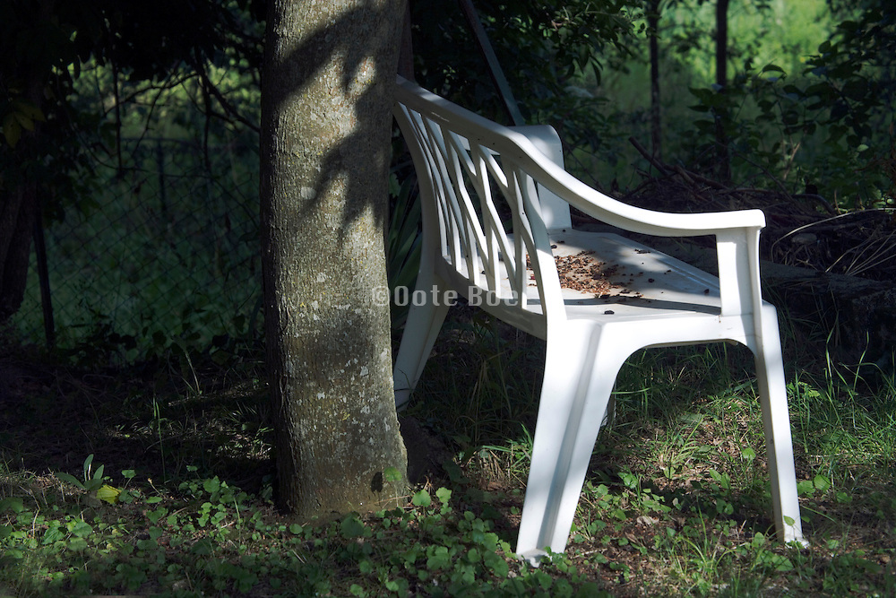 plastic two seater bench under a tree