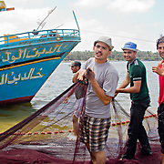 Bringing in their nets. Fishermen who choose to stay in Borg-Meghezil earn wages that depend on their catch and are paltry compared to what they can expect to be paid in Italy. For this reason, many boys and young have their eyes fixed firmly on migration by whatever means possible.
