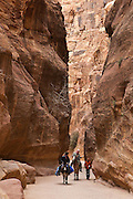 A young boy tries to sell postcards to passing horsemen in Al Siq, the slot canyon entrance to Petra, Jordan.