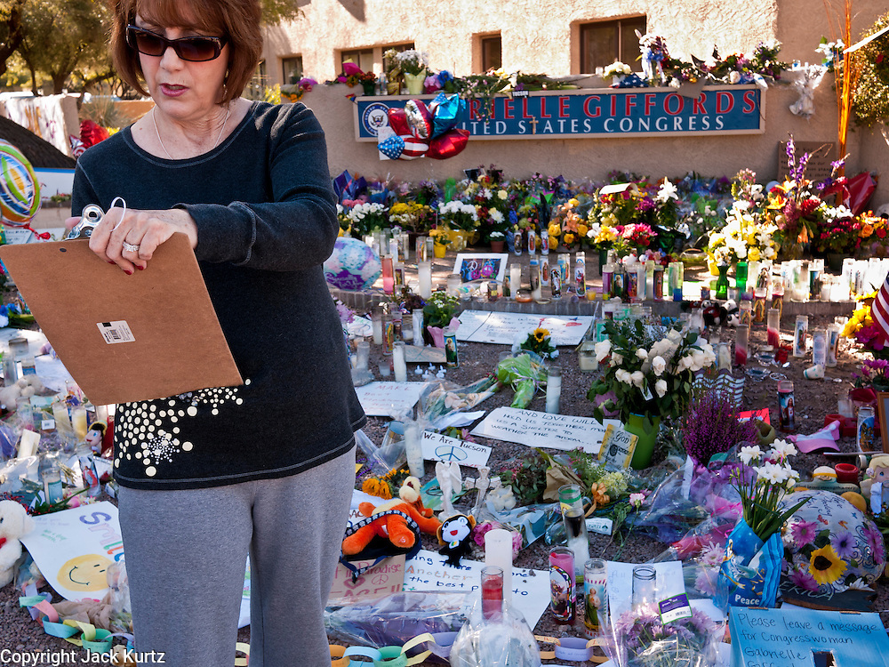 """15 JANUARY 2010 - TUCSON, AZ:    A woman writes a note for Congresswoman Gabrielle Giffords in front of a memorial at Giffords' office in Tucson, AZ, Saturday, January 15. Six people were killed and 14 injured in the shooting spree at a """"Congress on Your Corner"""" event hosted by Arizona Congresswoman Gabrielle Giffords at a Safeway grocery store in north Tucson on January 8. Congresswoman Giffords, the intended target of the attack, was shot in the head and seriously injured in the attack but is recovering. Doctors announced that they removed her breathing tube Saturday, one week after the attack. The alleged gunman, Jared Lee Loughner, was wrestled to the ground by bystanders when he stopped shooting to reload the Glock 19 semi-automatic pistol. Loughner is currently in federal custody at a medium security prison near Phoenix.PHOTO BY JACK KURTZ"""