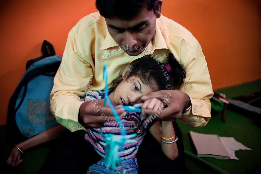 A disabled girl is receiving therapy inside Chingari Trust, the local NGO caring for disabled  children in Bhopal, Madhya Pradesh, India, near the abandoned Union Carbide (now DOW Chemical) industrial complex.