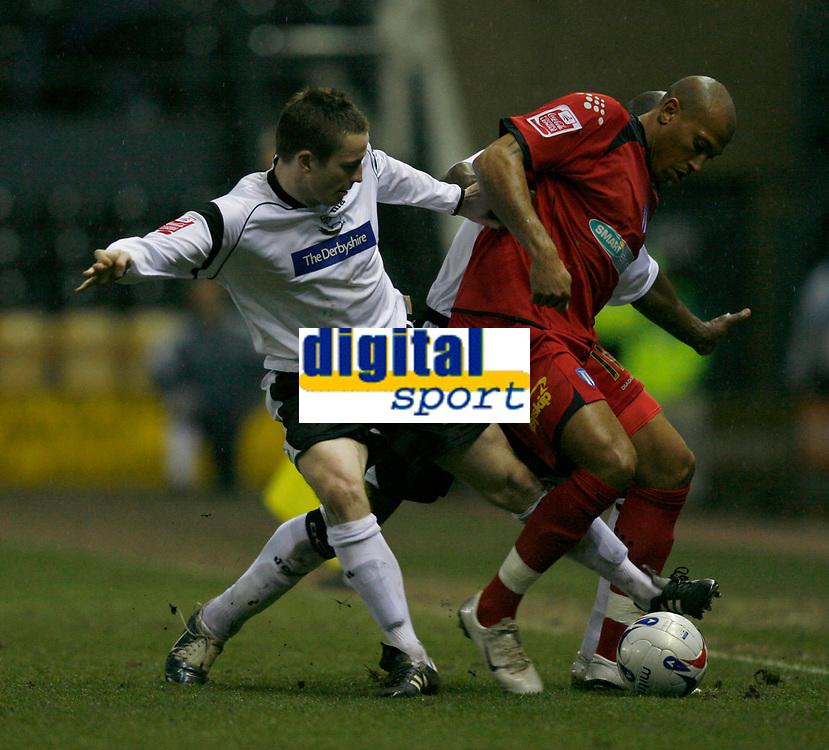 Matt Oakley (left) tackles Colchester sub Chris Iwelumo (right)