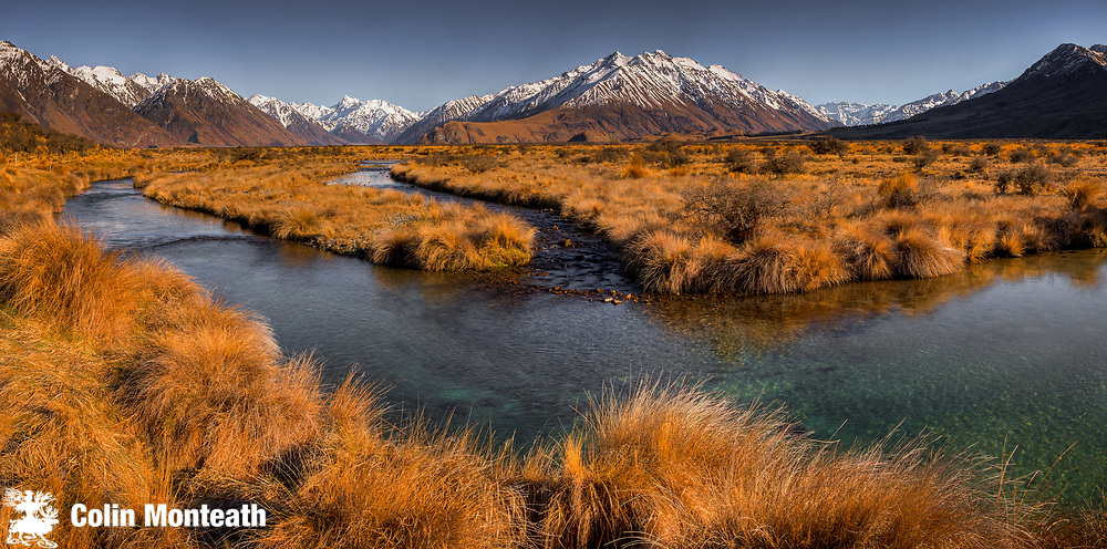 Tussock grass and braids of Rangitata river looking towards Erewhon Station and Mt D'Archiac, panorama from Mt Sunday, (Edoras village, Kingdom of Rohan in Lord of the Rings)  near Mt Potts Station, Canterbury, New Zealand