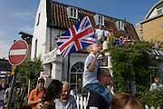 Young boy on father's shoulders hold flag aloft on the first day of competition of the London 2012 Olympic 250km mens' road race. Starting from central London and passing the capital's famous landmarks before heading out into rural England to the gruelling Box Hill in the county of Surrey. Local southwest Londoners lined the route hoping for British favourite Mark Cavendish to win Team GB first medal but were eventually disappointed when Kazakhstan's Alexandre Vinokourov eventually won gold.