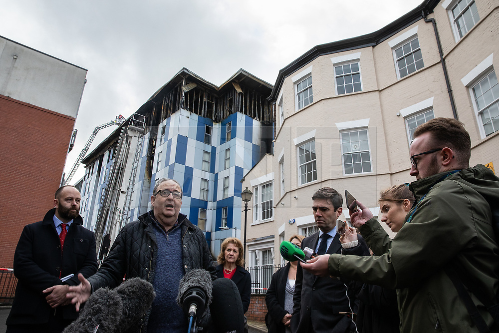"""© Licensed to London News Pictures. 16/11/2019. Bolton, UK. PAUL DENNETT of Greater Manchester's High Rise Taskforce , DAVID GREENHALGH of Bolton Council , Deputy Mayor of Greater Manchester BEV HUGHES , Mayor of Manchester ANDY BURNHAM at a press conference at the site of the blaze . Firefighters work at the scene where a fire broke out overnight (15th/16th November 2019) at a block of flats known as """" The Cube """" , in Bolton Town Centre . At least two people are known to have been treated by paramedics at the scene of the six-story block , which is occupied by students of the University of Bolton . Photo credit: Joel Goodman/LNP"""