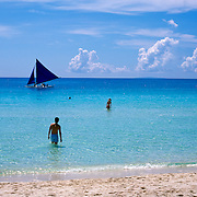 Asian tourists playing in the ocean at White Beach,  Boracay Island, the Philippines on October ,2, 2008, Photo Tim Clayton.....Asian tourists at White Beach, Boracay Island, the Philippines...The 4 km stretch of White beach on Boracay Island, the Philippines has been honoured as the best leisure destination in Asia beating popular destinations such as Bali in Indonesia and Sanya in China in a recent survey conducted by an International Travel Magazine with 2.2 million viewers taking part in the online poll...Last year, close to 600,000 visitors visited Boracay with South Korea providing 128,909 visitors followed by Japan, 35,294, USA, 13,362 and China 12,720...A popular destination for South Korean divers and honeymooners, Boracay is now attracting crowds of tourists from mainland China who are arriving in ever increasing numbers. In Asia, China has already overtaken Japan to become the largest source of outland travelers...Boracay's main attraction is 4 km of pristine powder fine white sand and the crystal clear azure water making it a popular destination for Scuba diving with nearly 20 dive centers along White beach. The stretch of shady palm trees separate the beach from the line of hotels, restaurants, bars and cafes. It's pulsating nightlife with the friendly locals make it increasingly popular with the asian tourists...The Boracay sailing boats provide endless tourist entertainment, particularly during the amazing sunsets when the silhouetted sails provide picture postcard scenes along the shoreline...Boracay Island is situated an hours flight from Manila and it's close proximity to South Korea, China, Taiwan and Japan means it is a growing destination for Asian tourists... By 2010, the island of Boracay expects to have 1,000,000 visitors.