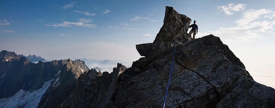 Jim Prager stands on the narrow summit of Mount Challenger, Picket Range, North Cascades National Park, Washington.
