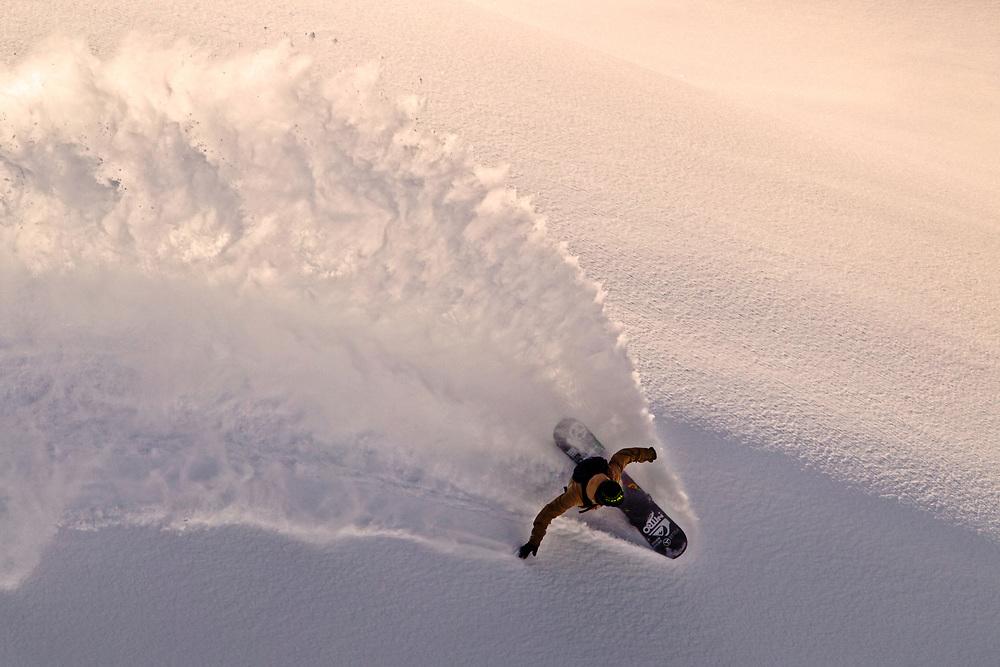 Professional snowboarder Bryan Fox slashes a ridge on his snowboard while heli-boarding in Alaska close to sunset.
