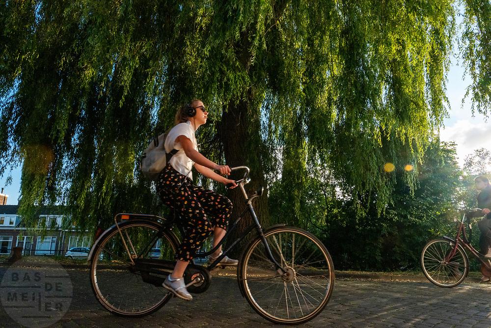 Een meisje fietst met een koptelefoon op door Utrecht.<br /> <br /> A girl cycles with her head phones on in Utrecht.