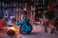 A woman tends to a cooking pot on a chilly morning in northern Laos