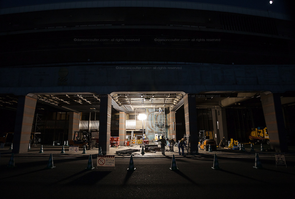 Workmen at night remodelling the National Stadium in Tokyo in readiness for the 2020 Olympic Games. Shinjuku, Tokyo, Japan, Friday October 3rd 2014