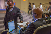 Purchase, NY – 31 October 2014. New York State Supreme Court Justic Bruce Tolver handing tally sheets from the judges to the scorekeeper. The Business Skills Olympics was founded by the African American Men of Westchester, is sponsored and facilitated by Morgan Stanley, and is open to high school teams in Westchester County.