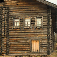 Finely-crafted windows punctuate the log wall of an historic house relocated to the Malye Korely outdoor museum, in a taiga forest near the northern port of Arkhangel'sk.