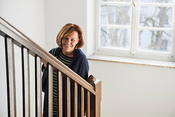 Happy senior woman wearing winter coat moving down on a staircase, Munich, Bavaria, Germany