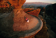 A Bedouin man on top of one of the ancient buildings of Petra, Jordan.