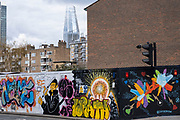 Hoarding covered in street art on a site near a range of housing both high rise and low rise in Waterloo on 13th April 2021 in London, United Kingdom.