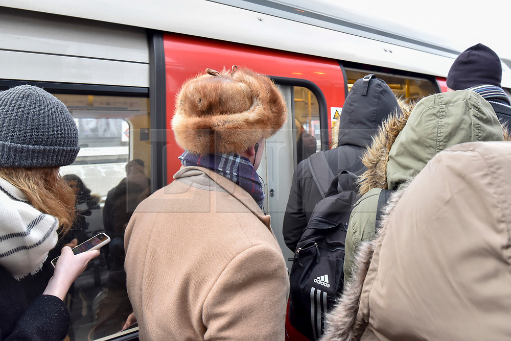 """© Licensed to London News Pictures. 26/02/2018. LONDON, UK. Morning commuters are forced to crowd onto the platforms at Harrow on the Hill station in north west London during rush hour as they face long delays and cancelled tube trains due to a signal failure caused.  Their journey is made more difficult with snow flurries and freezing temperatures brought about by """"The Beast From The East"""" arctic weather which has arrived in the UK.  Photo credit: Stephen Chung/LNP"""