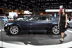 """12 February 2015:   A female model shows off a 2015 CHRYSLER 300: MoPar fans visiting the 2015 Chicago Auto Show will be checking out the many refinements to the 2015 Chrysler 300 four-door sedan. Visually, the body is even more sculptural and expressive with bolder front grille, signature LED lighting, unique finishes and new wheel designs. Finishing the new 300 sedan's powerful rear stance is a new sculpted LED taillamp with an illuminated halo. All-new five-passenger interior includes a standard seven-inch full-color driver info display and class-exclusive electronic rotary transmission shifter. The popular Chrysler 300 is available in four highly equipped models: 300 Limited, 300S, 300C and 300C Platinum. The Chrysler 300 SRT8 is covered separately. For 2015, the Chrysler 300S combines an even more """"blacked out"""" look and new Ambassador Blue sport interior, with benchmark levels of quality, technology and craftsmanship. Large 20-inch polished-face wheels are for rear-wheel drive only, and the 19-inch with all-wheel drive, provides the sedans with an even more planted and road-holding look. Also, the Chrysler 300 AWD model offers even more all-season capability, and includes an exclusive active transfer case and front-axle disconnect for greater fuel economy. New 2015 Chrysler 300 rear-wheel drive or AWD models with the 292 horsepower (300 horsepower on 300S model) 3.6-liter Pentastar V-6 engine continue to use the TorqueFlite eight-speed transmission. Optional powerplant on all 300 models is the 363-hp 5.7L Hemi V-8. Beats by Dr. Dre audio technology that includes a 522-watt 12-channel amplifier is standard on the Chrysler 300S and available on other 300 models. Every '15 Chrysler 300 variant is outfitted with a tailored trunk that can handle 16.3 cubic feet of luggage.<br /> <br /> First staged in 1901, the Chicago Auto Show is the largest auto show in North America and has been held more times than any other auto exposition on the continent. The 2015 show marks"""