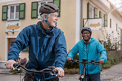 Male friends cycling on road, Bavaria, Germany