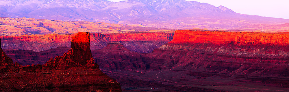 Warm light from the setting sun highlights canyon rims overlooking the Colorado River near Moab, Utah. The La Sal Mountains are visible in the background.<br /> WATERMARKS WILL NOT APPEAR ON PRINTS OR LICENSED IMAGES.