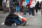 Homeless man busking to make a little money by making music with his voice through a traffic cone on a busy Oxford Street in London, amidst the bustle of passers by.