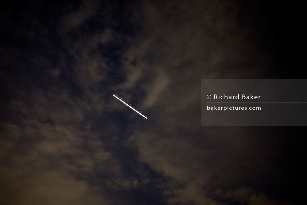 The lights from a jet airliner trail themselves during a long, hand-held time exposure above London skies.