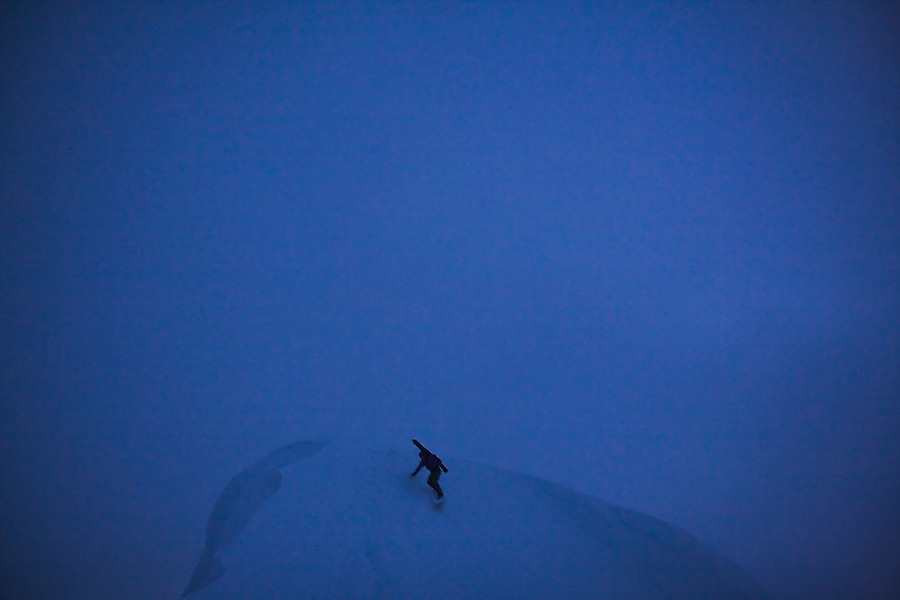A young man drops off a ridge with his snowboard  to catch some turns in the Mount Baker backcountry, Washington.