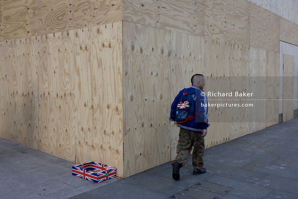 Man with Union Jack rusksack and a matching discarded covered box left on the corner of construction hoarding plyboard in Trafalgar Square, London.