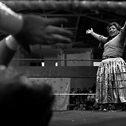 Carman Rosa celebrates victory over her male counterpart as her tag team mate Yolanda La Amorosa looks on during the 'Titans of the Ring' wrestling group's Sunday performance at El Alto's Multifunctional Centre. Bolivia. The wrestling group includes the fighting Cholitas, a group of Indigenous Female Lucha Libra wrestlers who fight the men as well as each other for just a few dollars appearance money. El Alto, Bolivia, 11th April 2010. Photo Tim Clayton