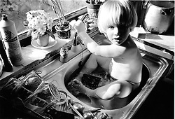 Young child sitting in kitchen sink,