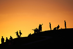 United States, Washington, Seattle. Sunset light silhouettes a variety of people on the hillside at Gasworks Park, Seattle, Washington.