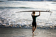 Female surfer entering ocean carrying surfboard over her head at Terramar Beach in Carlsbad,CA.<br /> <br /> THIS IMAGE ALSO AVAILABLE AS SIGNED, LIMITED EDITION PRINT. SERIES LIMITED TO 10. <br /> <br /> EMAIL RR@ROBERTRANDALL.COM FOR PRICING