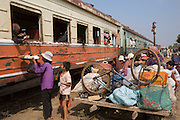 ROYAL CAMBODIAN RAILWAYS. The journey from Phnom Penh to Battambang is the last working route. A passenger train, operates only at weekends. A Czech made diesel locomotive, leaves the capital Saturday morning, arriving in Battambang 22 hours later in the dead of night, and returns on Sunday. Max speed is about 30kmh, often slower due to the track's terrible condition. Carriages are dilapidated, with holes in the floor and only spaces for windows. Passengers sit or sleep on hardwood bench seats, hammocks, or on the floor of cargo carriages. The drivers, controllers & guards add to their small monthly pay by charging for local passengers and cargo; from motor bikes and local produce to timber loaded aboard at the 30 stations along the route. This together with other trains and farm vehicles further slows the journey. In rural areas, the track is a lifeline, and used for local transport on 'bamboo trains' powered by belt-motors, or pushcarts. Boom towns, with a 'goldrush mentality' near the rapidly depleted rainforest, are a hive of activity, with logging as their resource, where children workers even gamble away their earnings on cardgames. In the city, the railway has a life of its own, where people live and work nearby or on the track itself. Market stalls, restaurants, chairs and tables, are removed only briefly, when the infrequent train passes!///Passengers are offered refreshments at Kampng Chnang station. A bamboo train is loaded nearby
