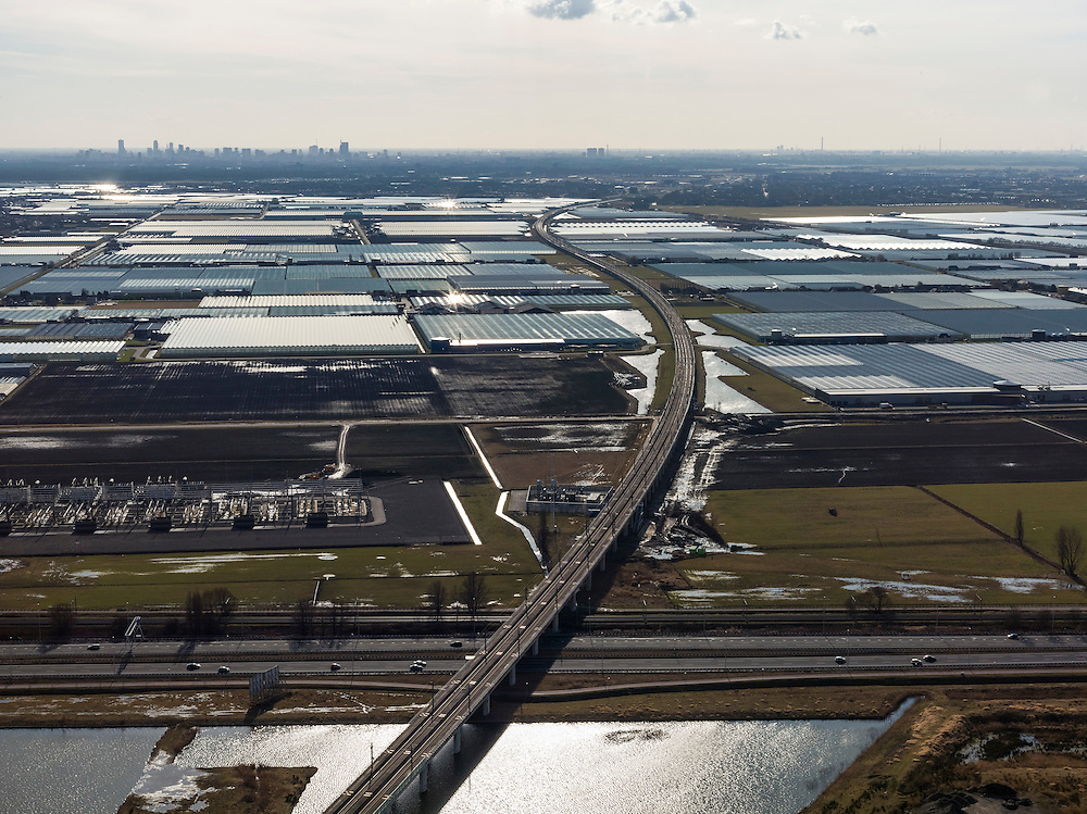 Nederland, Zuid-Holland, Zoetermeer, 20-02-2012; HSL over A12 doorsnijdt het kassengebeid van Bleiswijk in de Overbuurtsche Polder, skyline Rotterdam.The rails of the HST between the greenhouses of the vegetables and fruit producers in the west of the Netherlands, skyline Rotterdam..copyright foto/photo Siebe Swart