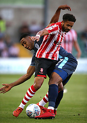Lincoln City's Bruno Andrade (front) and Bury's Gold Omotayo battle for the ball