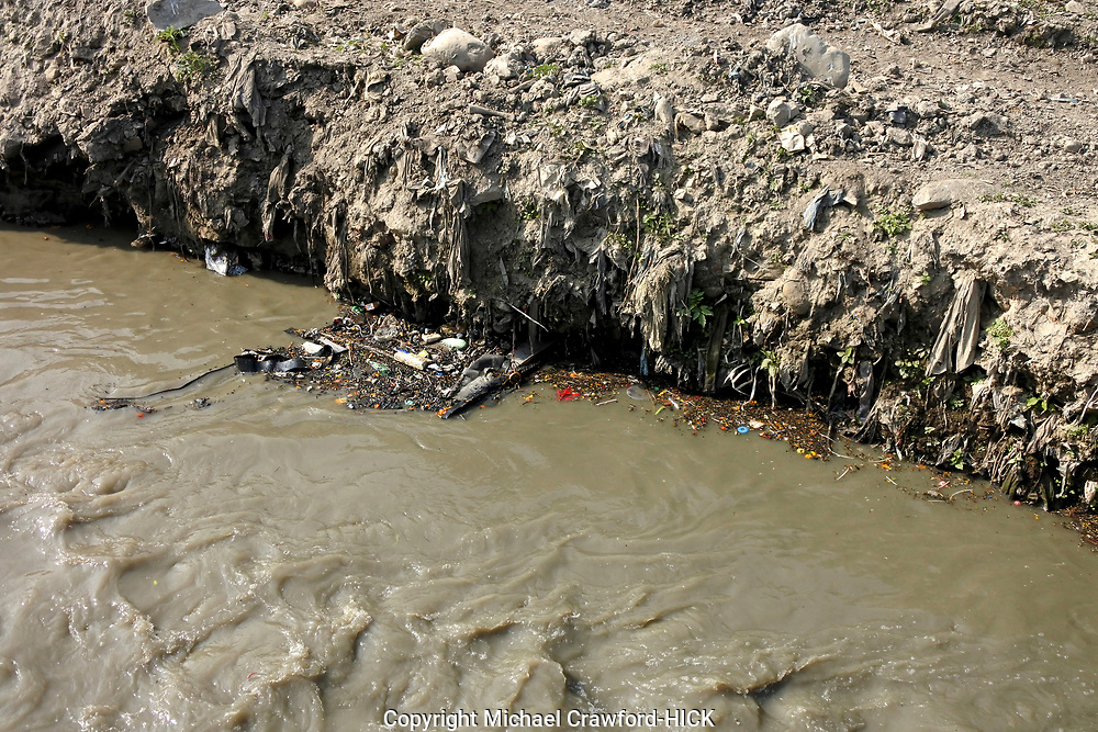 Mounts of plastic bags, dust and build up over many years in a river bed