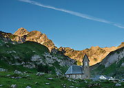 "At Meglisalp, Altmann peak (2435m) rises dramatically above a 1904 mountain chapel (Kapelle Maria zum Schnee, ""Holy Mother Mary of the Snow""). Berggasthaus Meglisalp can only be reached on foot in the heart of the Alpstein mountain chain in the Appenzell Alps, Switzerland, Europe. This authentic mountain hostelry, owned by the same family for five generations, dates from 1897. Meglisalp is a working family dairy farm."