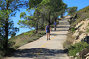 Two women walking along mountain path from Coll de Rates, Tarbena, Marina Alta, Alicante province, Spain