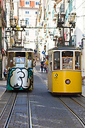 Funiculars - Elevador da Bica, pass carrying local people and tourists on tram tracks on steep hill in City of Lisbon, Portugal