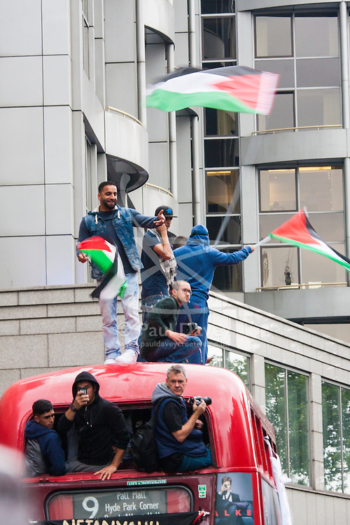 London, July 11th 2014. Protesters climb atop a Routemaster bus as thousands of Palestinians and their supporters demonstrate against the latest wave of Israeli retaliatory attacks on Palestinian targets and homes, where casualties are steadily mounting.