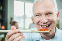 Portrait of mature man tasting food, close up