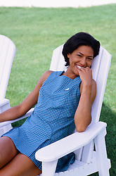 African American woman smiling and sitting in an adirondack chair outdoors