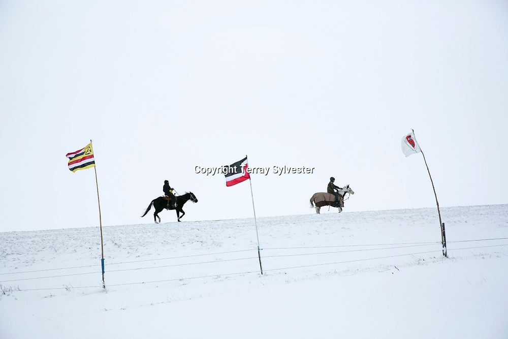Horsemen ride behind tribal flags on the outskirts of the opposition camp agains the Dakota Access oil pipeline on November 30, 2016. Cannon Ball, North Dakota, United States.