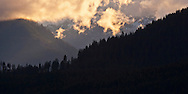 The Hamma Hamma River Valley as viewed fromt he Kitsap Peninsula in Puget Sound showing forested foothills and partially snowcovered mountains in the distance with evening alpenglow warmed clouds over the valley.  Olympic National Forest, Washington, USA panorama