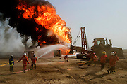 For five days in a row, Kuwait firefighters attempted without success to kill an oil well fire in the Rumaila field placed by retreating Iraqi troops. The Rumaila field is one of Iraq's biggest oil fields with five billion barrels in reserve. Many of the wells are 10,000 feet deep and produce huge volumes of oil and gas under tremendous pressure, which makes capping them very difficult and dangerous. Rumaila is also spelled Rumeilah.