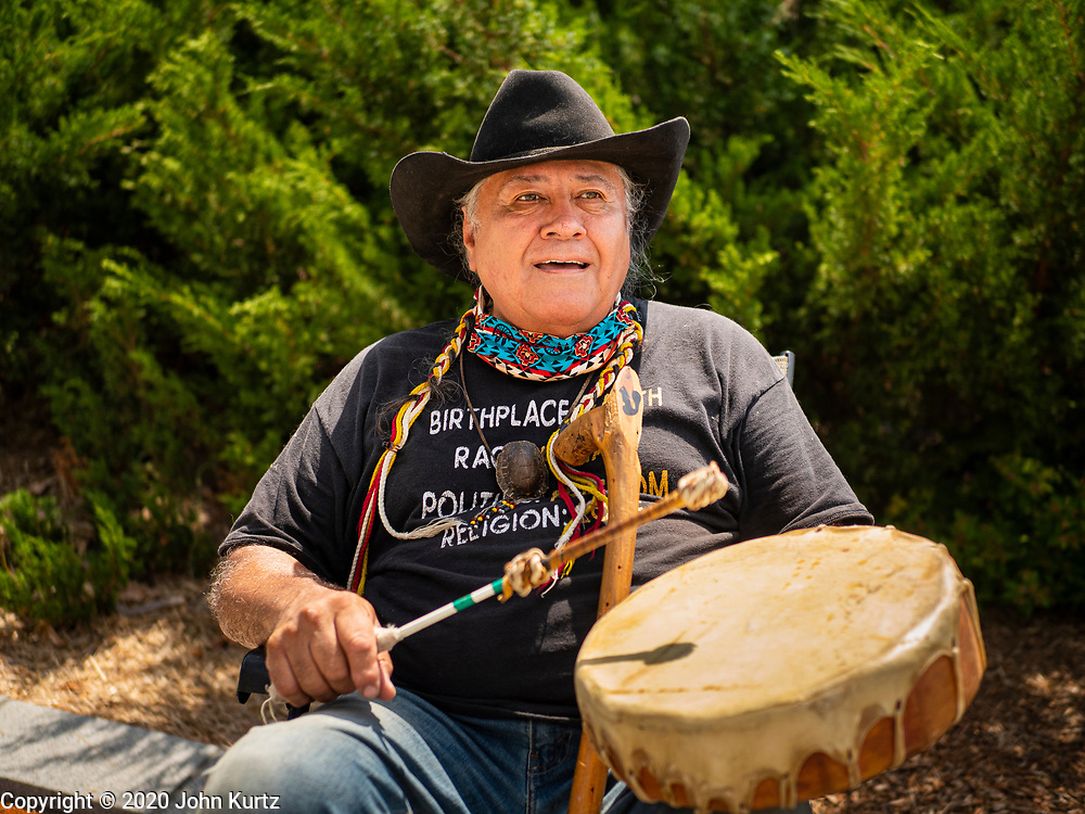 04 JULY 2020 - DES MOINES, IOWA: A member of the Meskwaki Nation, a Native American nation in Iowa, drums and prays before a protest Saturday. Hundreds of people came to the grounds of the Iowa State Capitol to protest against and in favor of historic monuments on the capitol grounds. Several hundred people protested against a monument to Christopher Columbus and the stereotypical depiction of Native Americans on the capitol grounds. About 50 people came to the capitol to rally in support of the monuments. The protest against the monuments was organized by Seeding Sovereignty, a collective of indigenous women. The rally to defend the monuments was organized by an Iowa chapter of Three Percenters.     PHOTO BY JACK KURTZ
