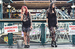 © licensed to London News Pictures. 26/09/2014<br /> The 10th London International Tattoo Convention, one of the most prestigious body art conventions in the world, brought together 400 of the best tattoo artists to thousands of admirers at Tobacco Dock. Other attractions and alternative performances included burlesque, sword swallowing, striptease dancers, fire-dancers and trapeze performers. Pictured.Tattoo fans take a break at the convention.<br /> Photo credit : Ian Whittaker/LNP