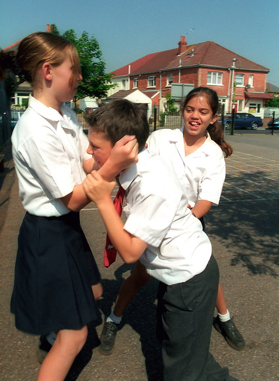 Girls bullying  a younger boy at school, posed by models